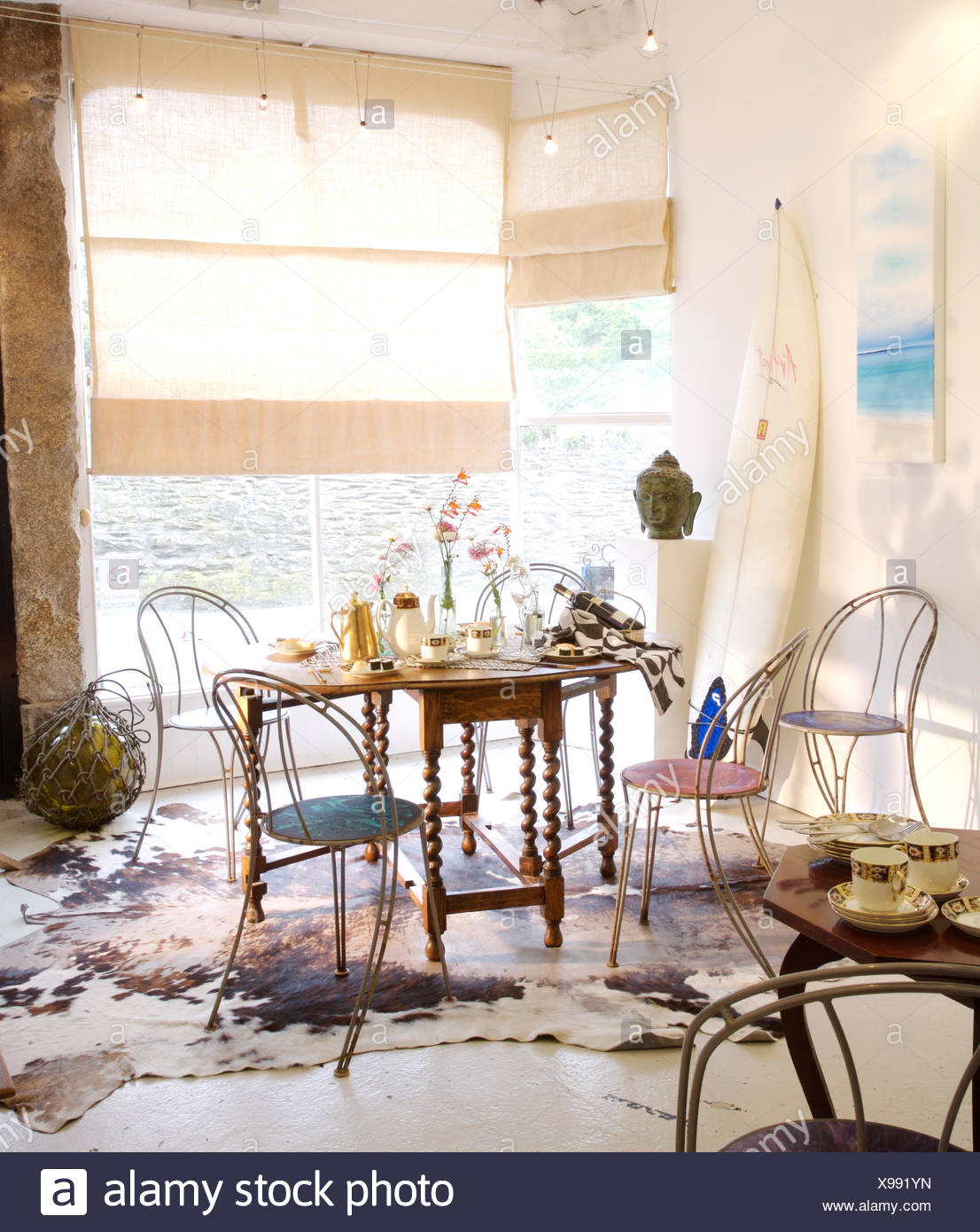 Metal chairs at Jacobean style table in coastal dining room with rough linen blinds and a vintage cow hide rug Stock Photo