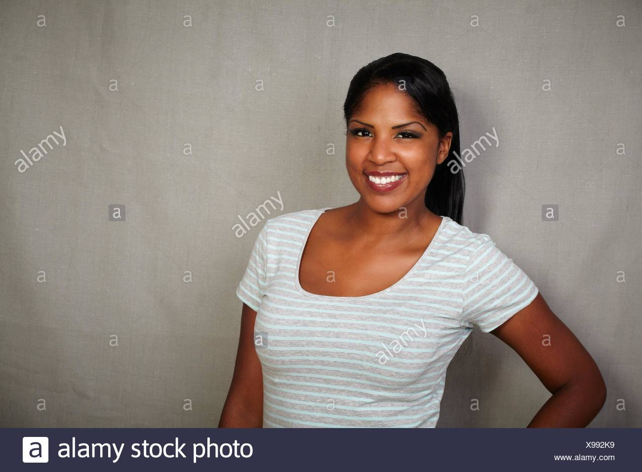 Charismatic girl of african ethnicity standing against grey background - copy space. - Stock Image