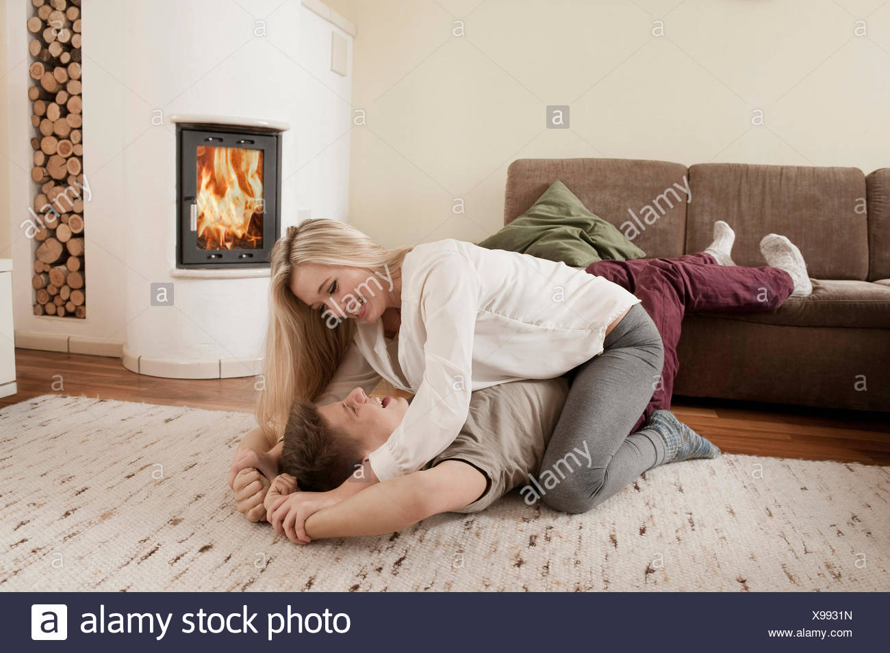 Teenage couple playfighting on carpet in front of fireside - Stock Image