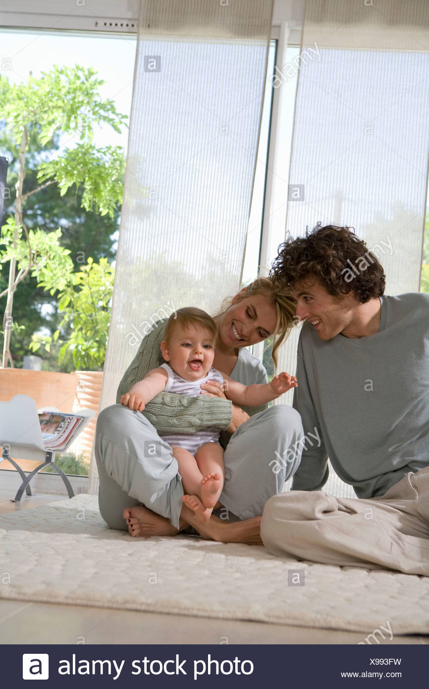 Parents laugh with baby on floor - Stock Image