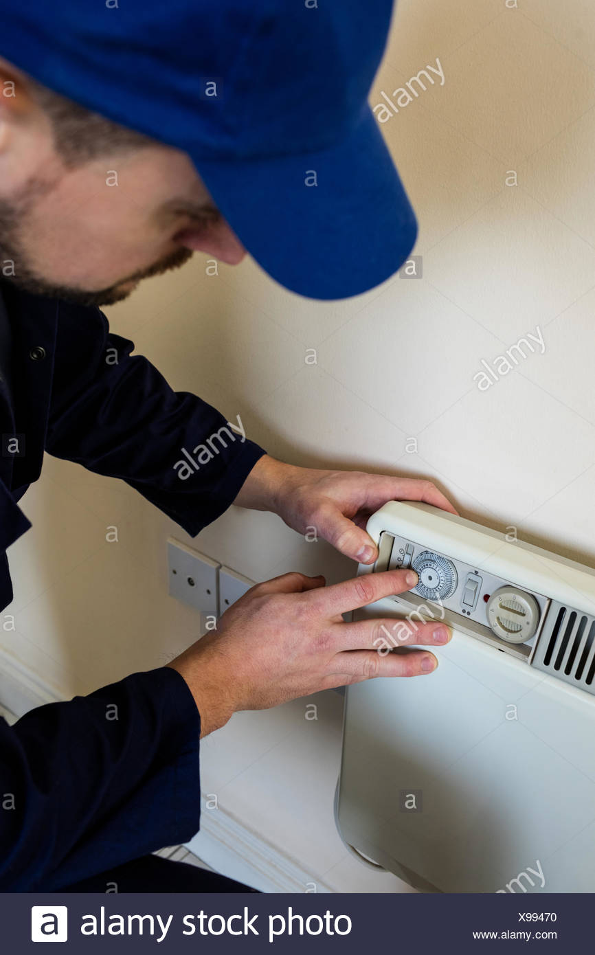 Handyman testing air conditioner - Stock Image