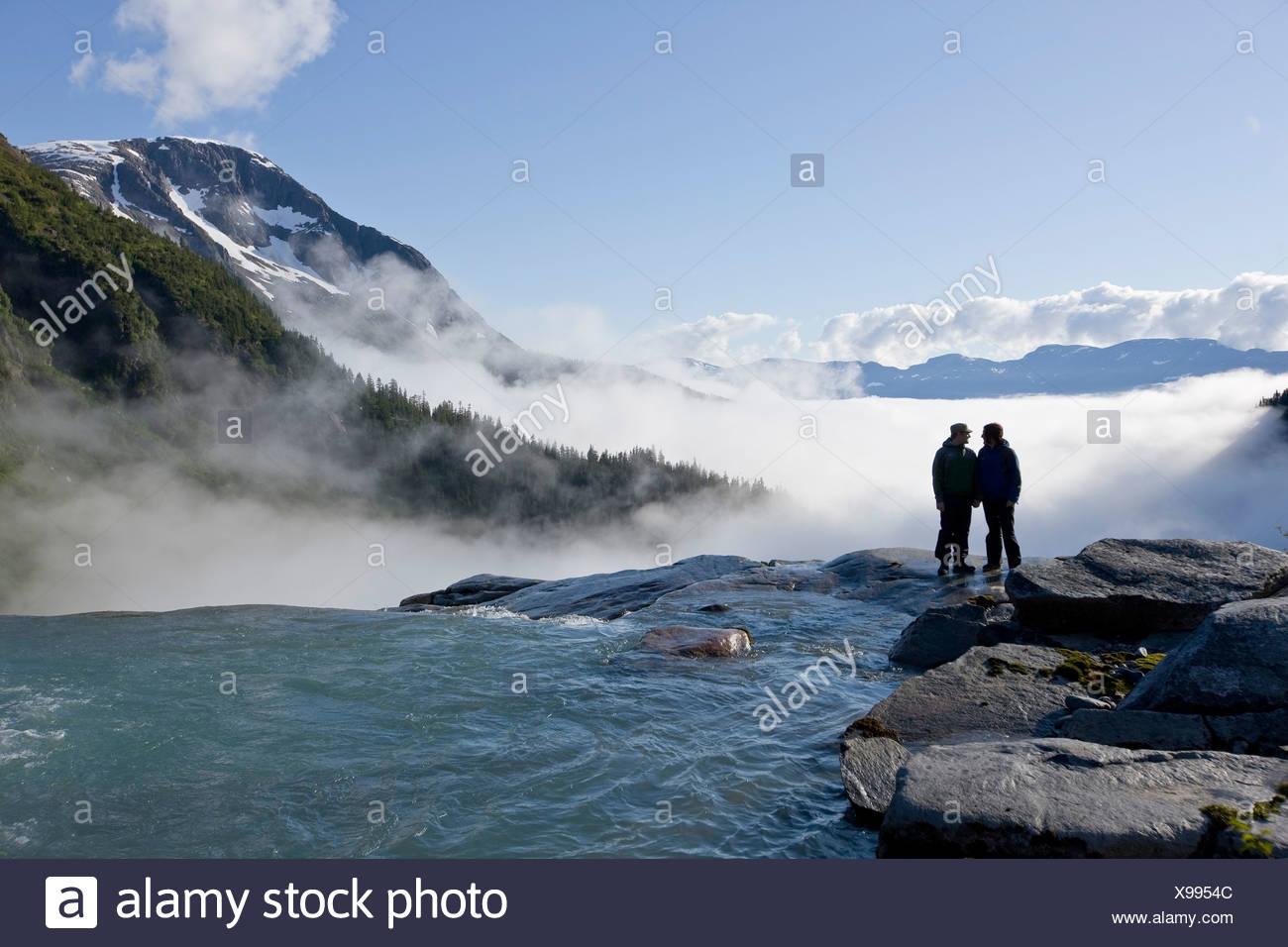 Two people overlook the brink of Sockeye Falls originating in the Juneau Icefield, Taku River Valley below in Southeast Alaska - Stock Image
