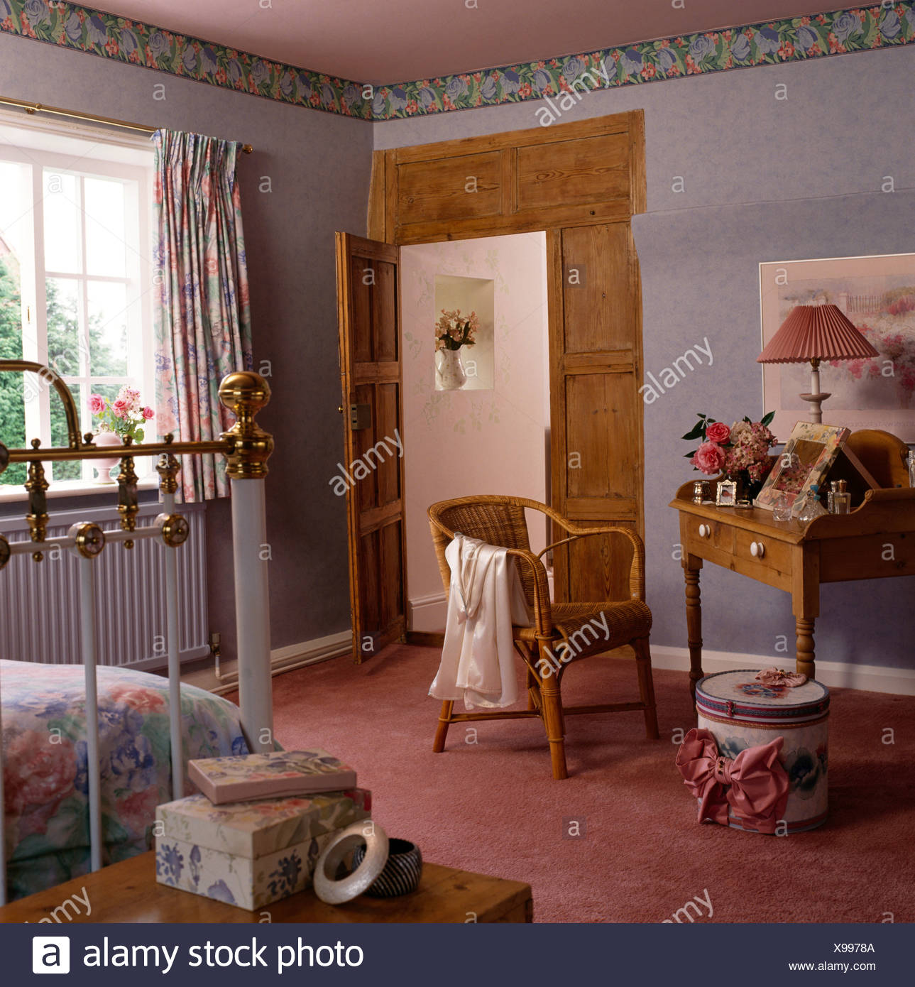 Wicker Chair And Pine Dressing Table In Cottage Bedroom With Wallpaper Border And Stripped Pine Doorway Stock Photo Alamy