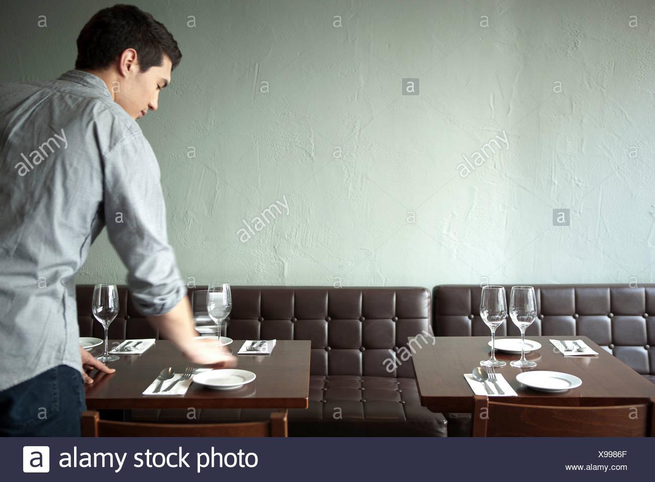 Waiter setting table in restaurant - Stock Image