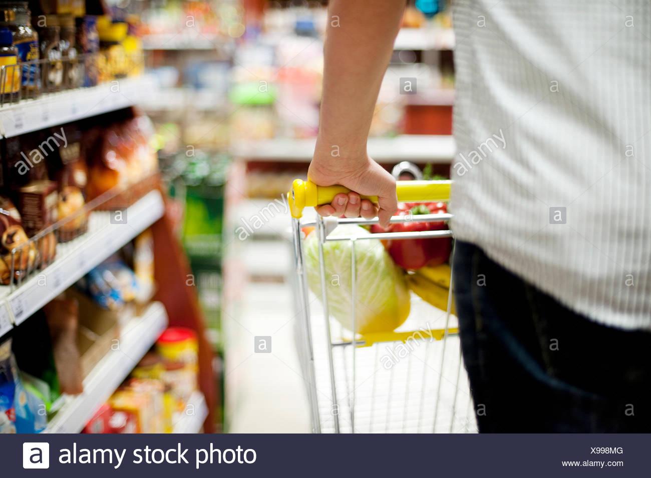 Man pushing shopping trolley Debica, Poland Stock Photo