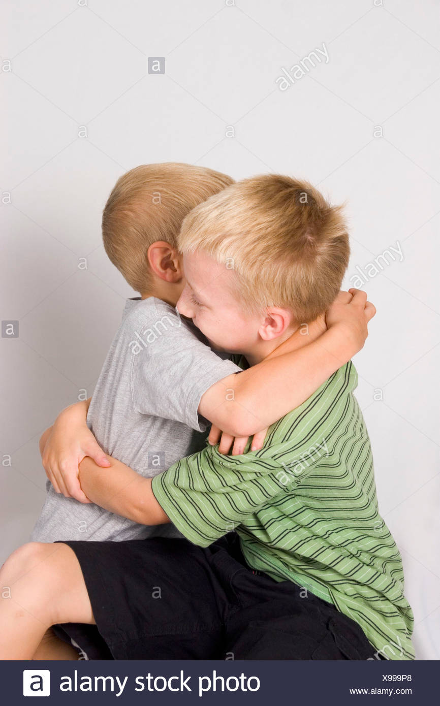 A pair of young blond haired boys, brothers, embrace against a pale background - Stock Image