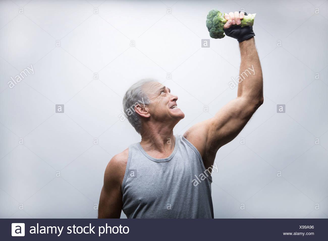 Senior man looking up and lifting broccoli - Stock Image