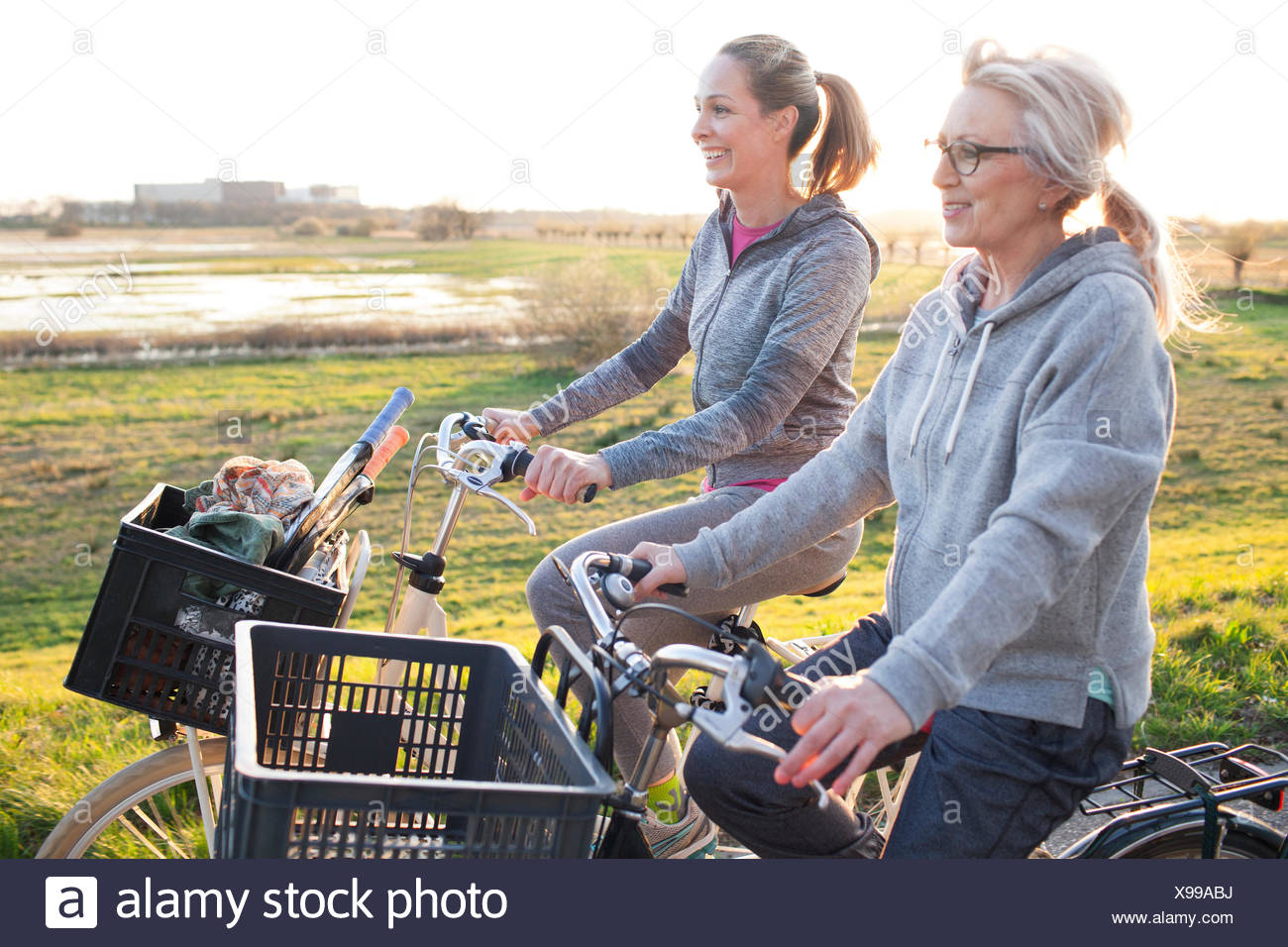 Side view of women cycling by marshland smiling - Stock Image