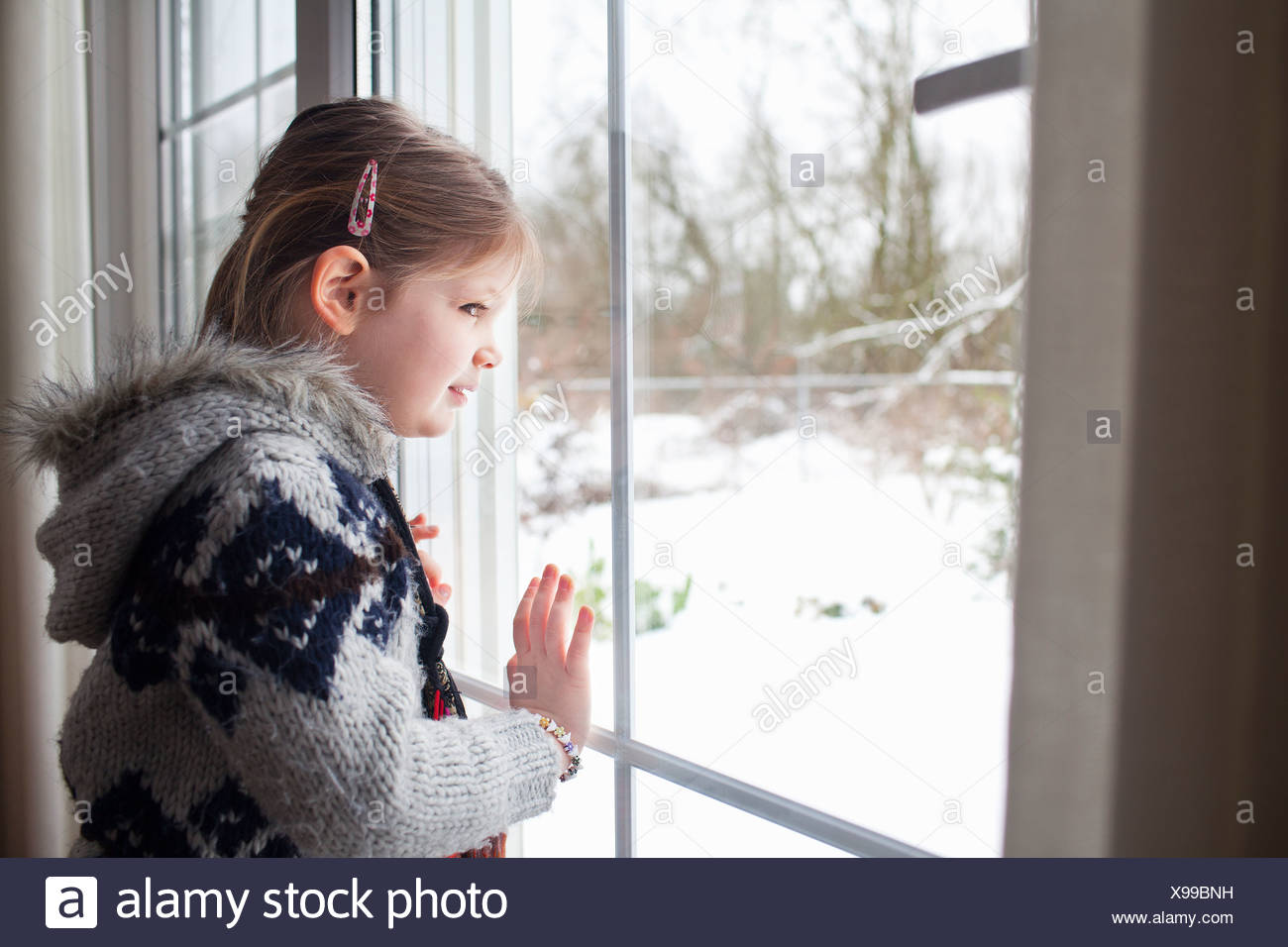 Young girl looking out of window at garden in snow - Stock Image