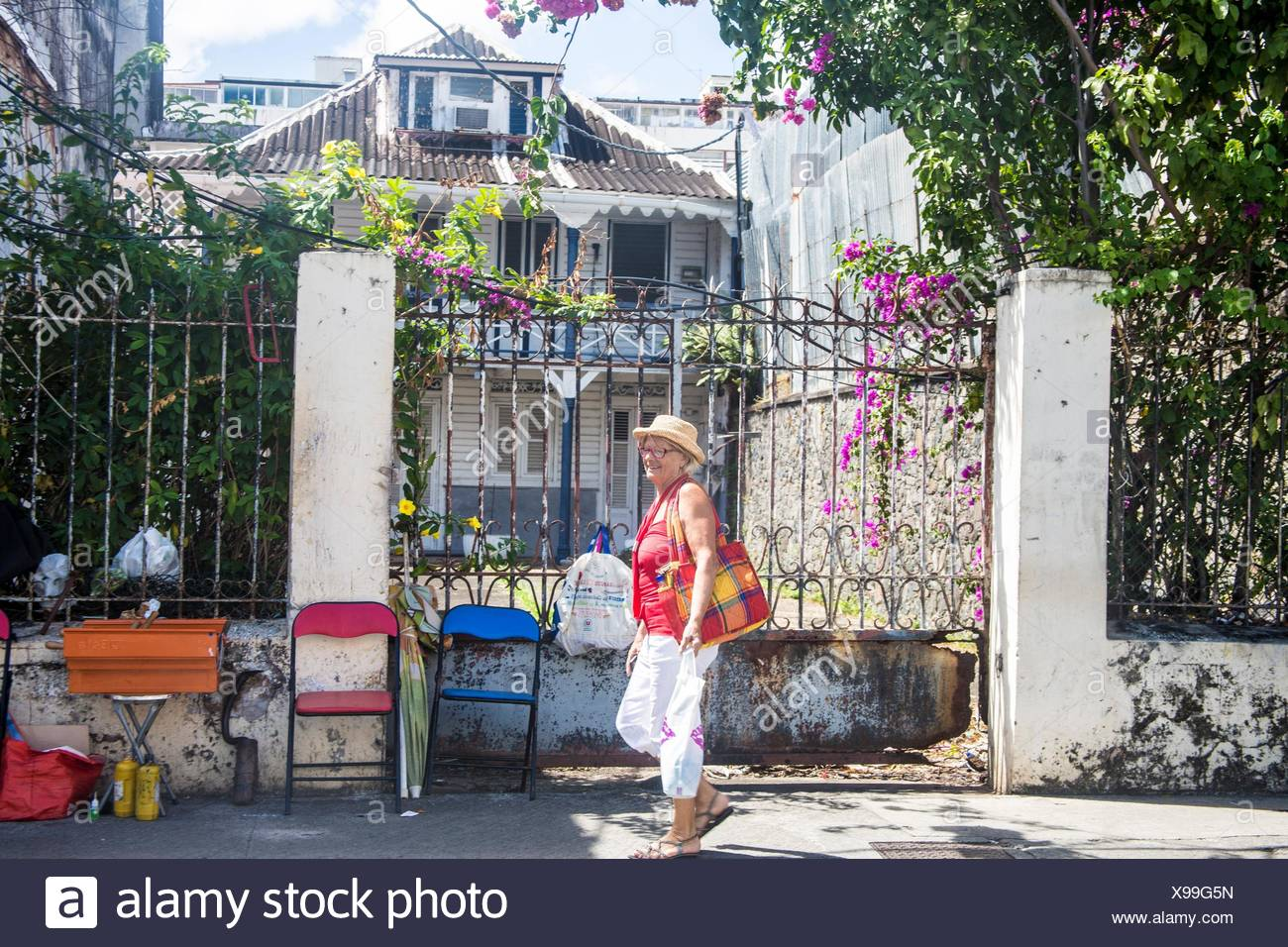 Caucasian older senior retired woman walking the streets of fort de france in Martinique in front of an iron gate. SHe has a straw hat and shopping - Stock Image