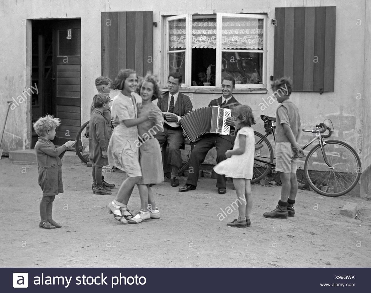 Zwei Männer machen Musik und Kinder tanzen dazu im Hof, Deutschland 1930er Jahre. Two men making music and children dancing at the courtyard, Germany 1930s. - Stock Image