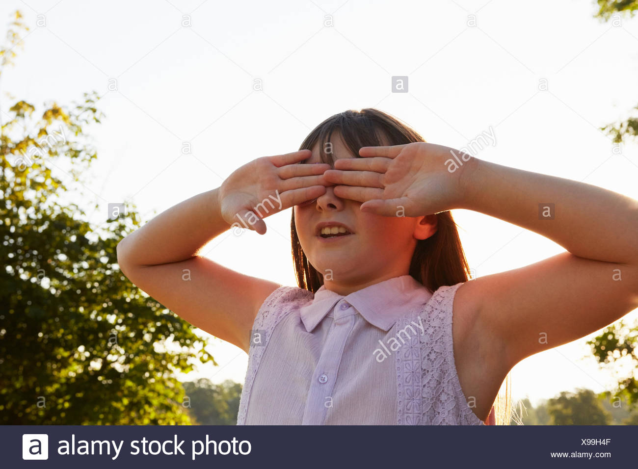 Girl covering eyes for hide and seek in park Stock Photo