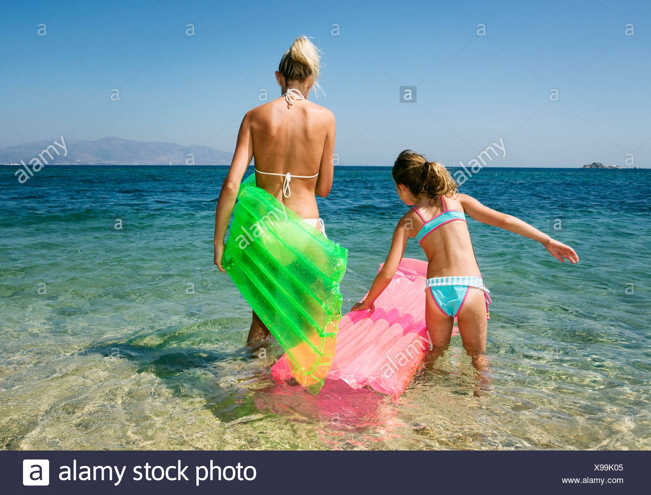 Woman with young girl at the beach with inflatable rafts. Stock Photo