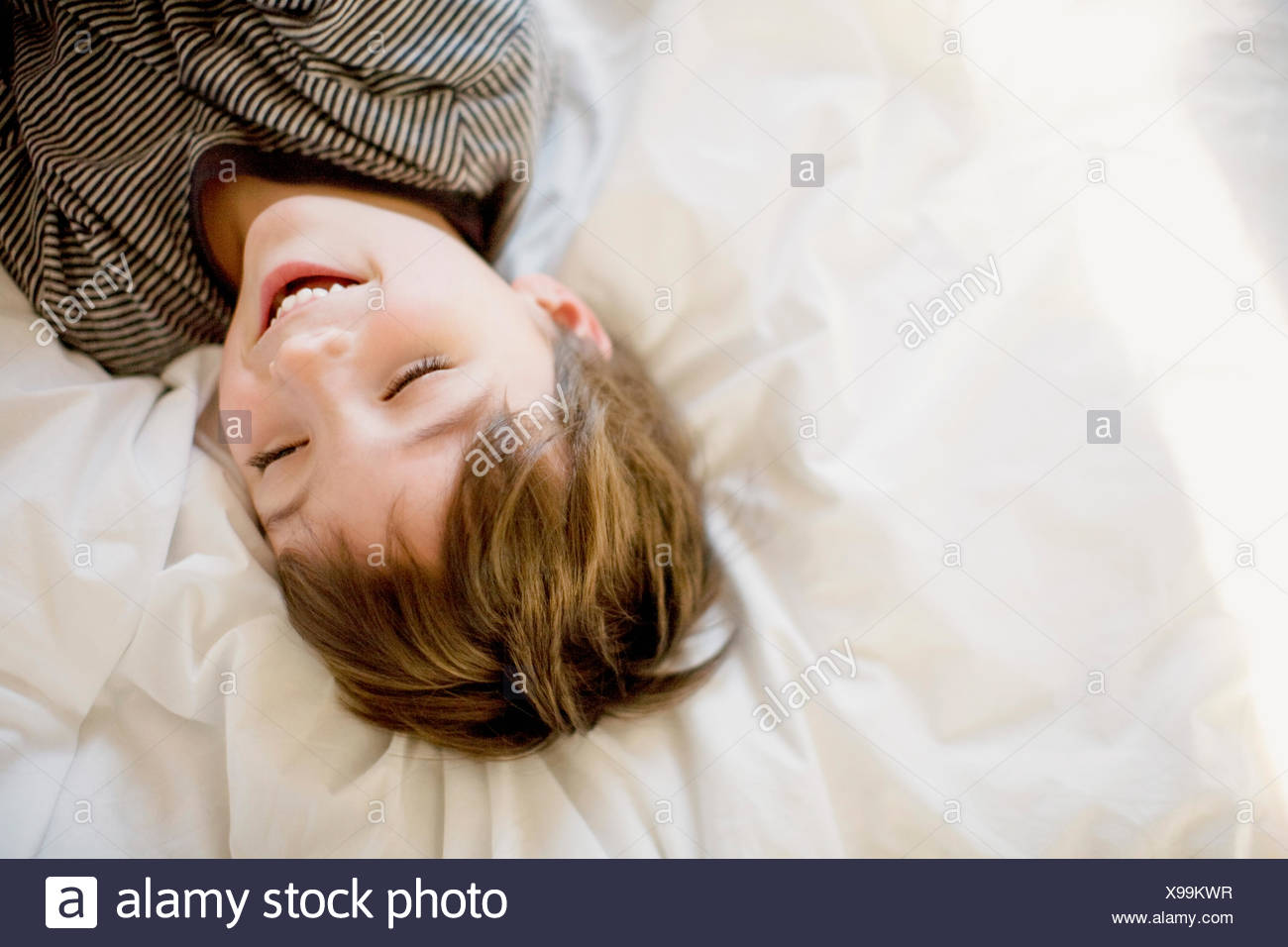 Happy boy lying on the bed - Stock Image