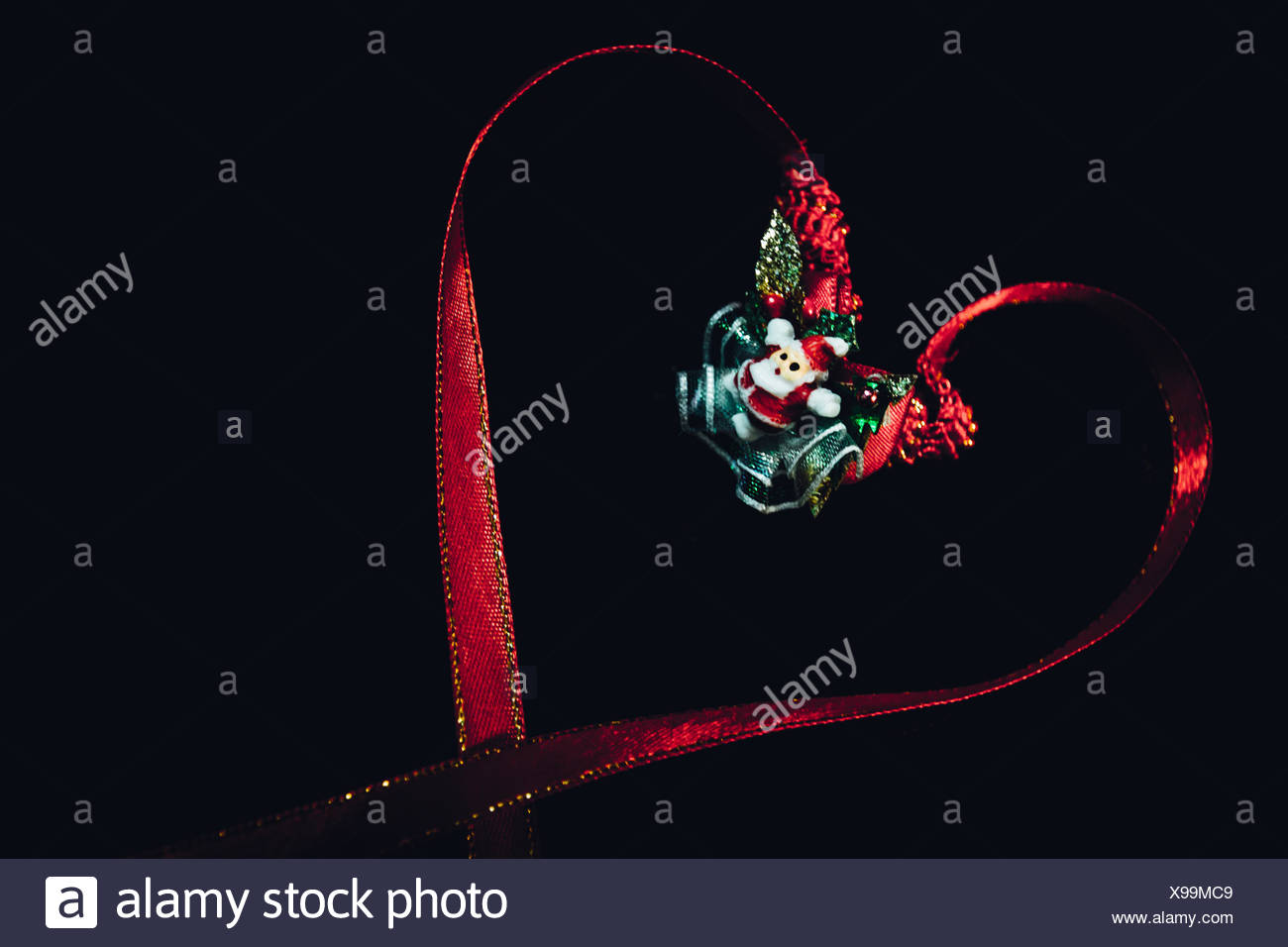 Close-Up Of Hear Shaped Christmas Decoration Against Black Background - Stock Image