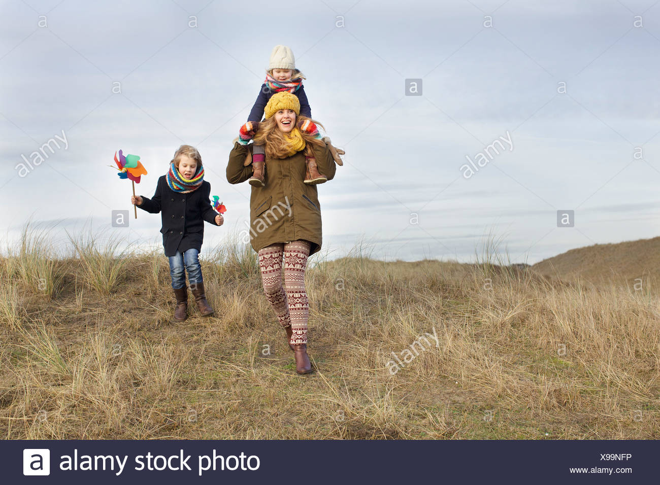 Smiling mid adult woman with daughter and son at coast - Stock Image