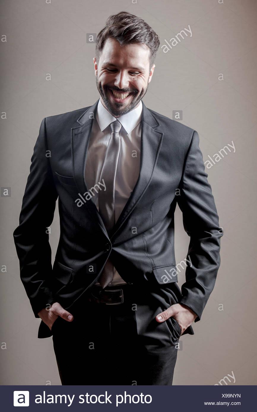 Businessman rejoicing hands in pockets - Stock Image