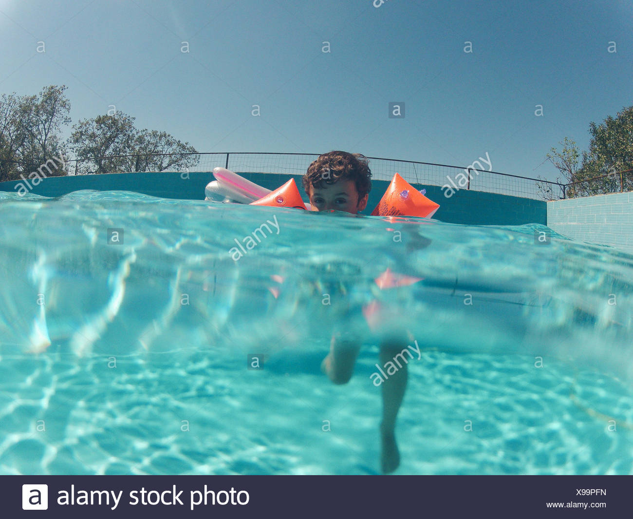 Portrait Of Boy Swimming In Pool Against Sky - Stock Image