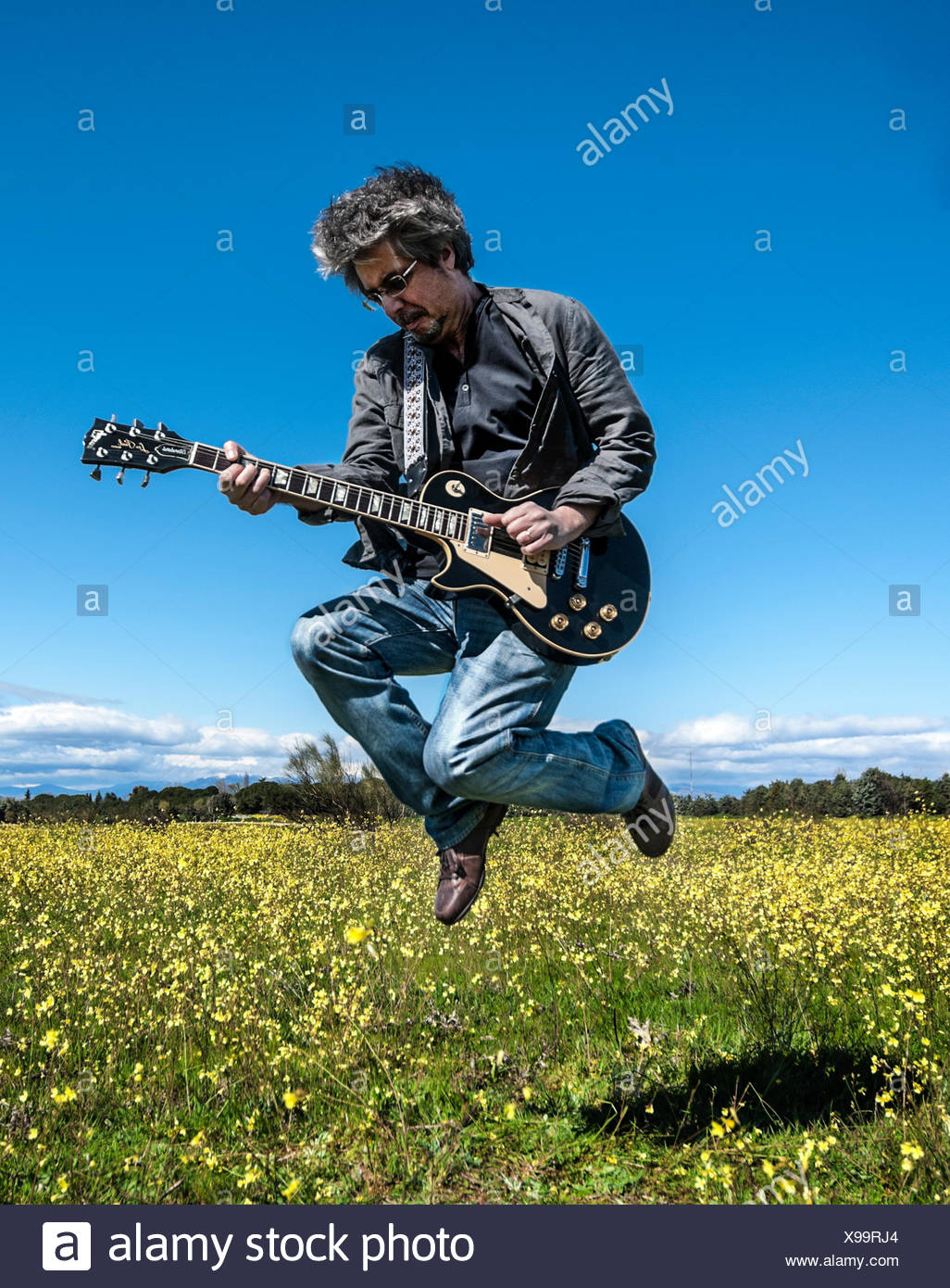 Man in leather jacket playing guitar - Stock Image