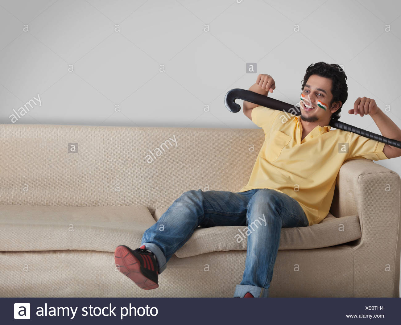 Young man in casuals on sofa looking away while holding hockey stick - Stock Image