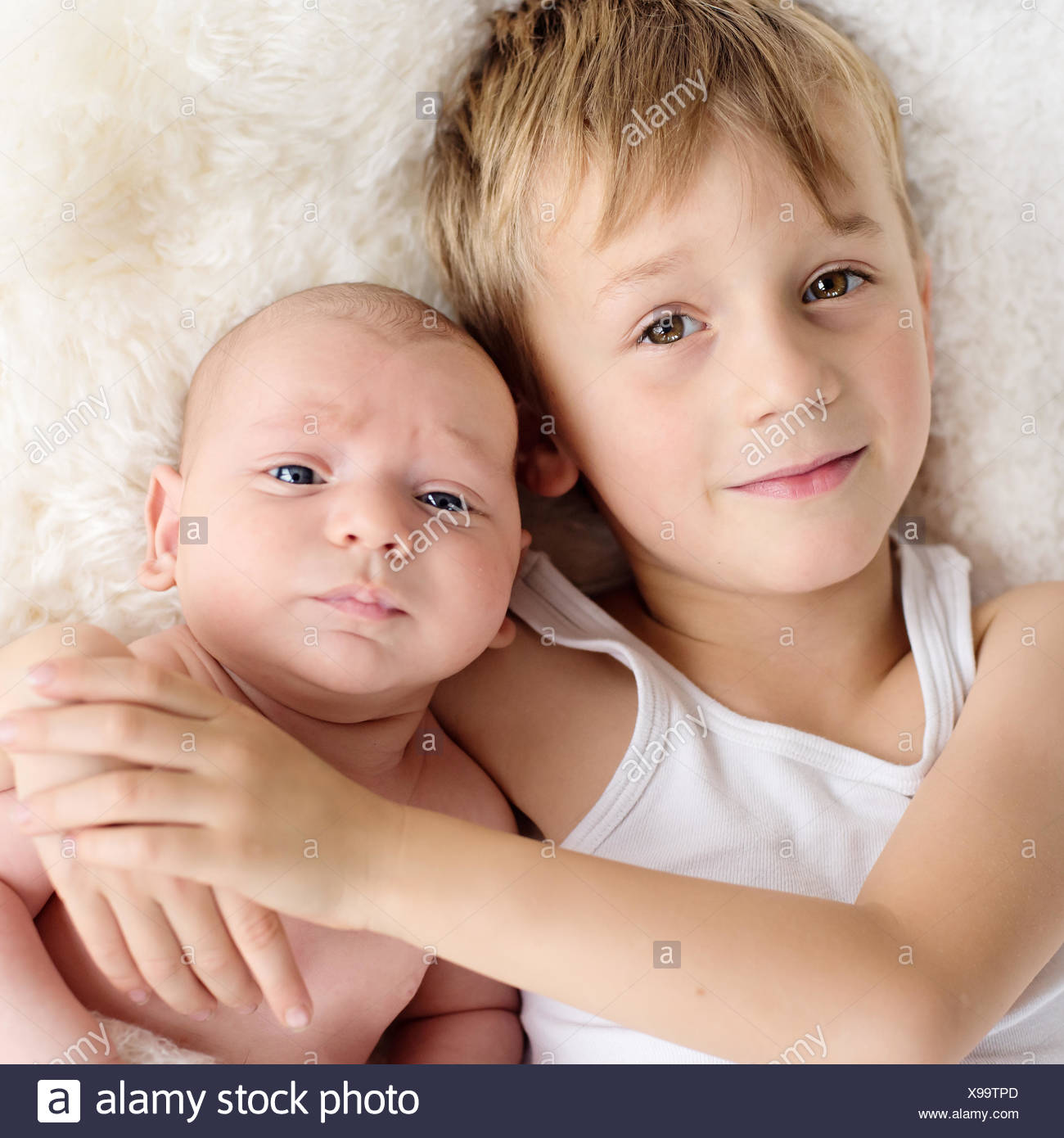 Boy cuddling his baby brother - Stock Image