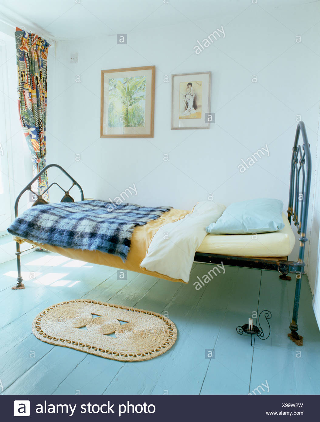 Single Cast Iron Bed With Blue Checked Throw In Simple White Bedroom With Small Rug On Pastel Blue Painted Wooden Flooring Stock Photo Alamy