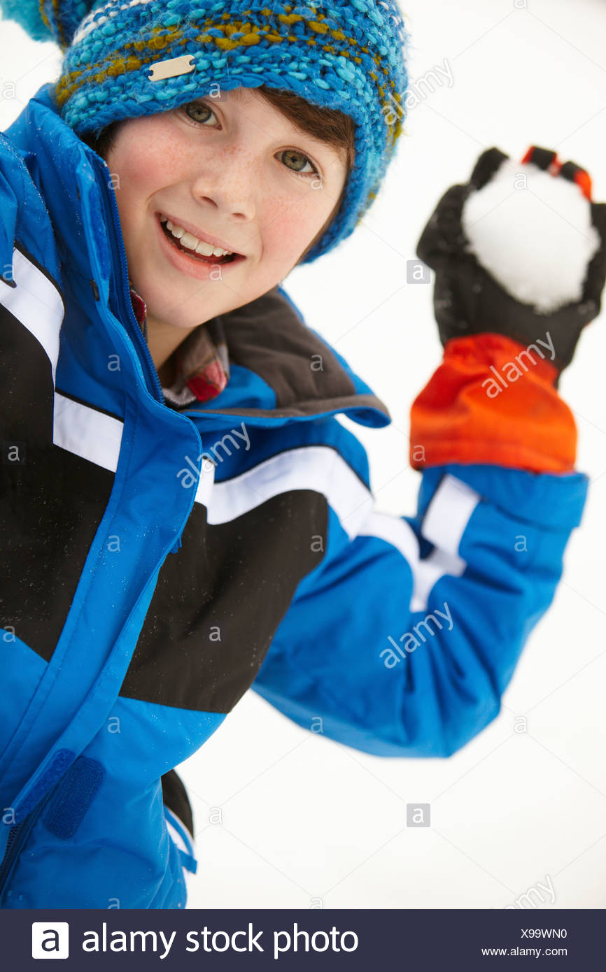 Young Boy About To Throw Snowball Wearing Woolly Hat - Stock Image