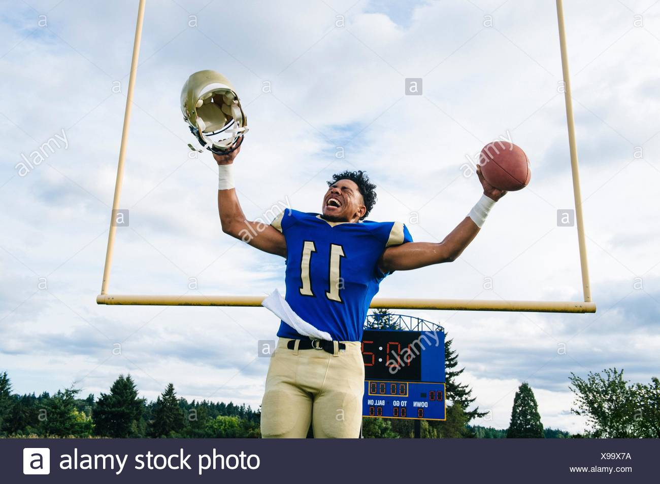Teenage American football player celebrating on soccer pitch - Stock Image