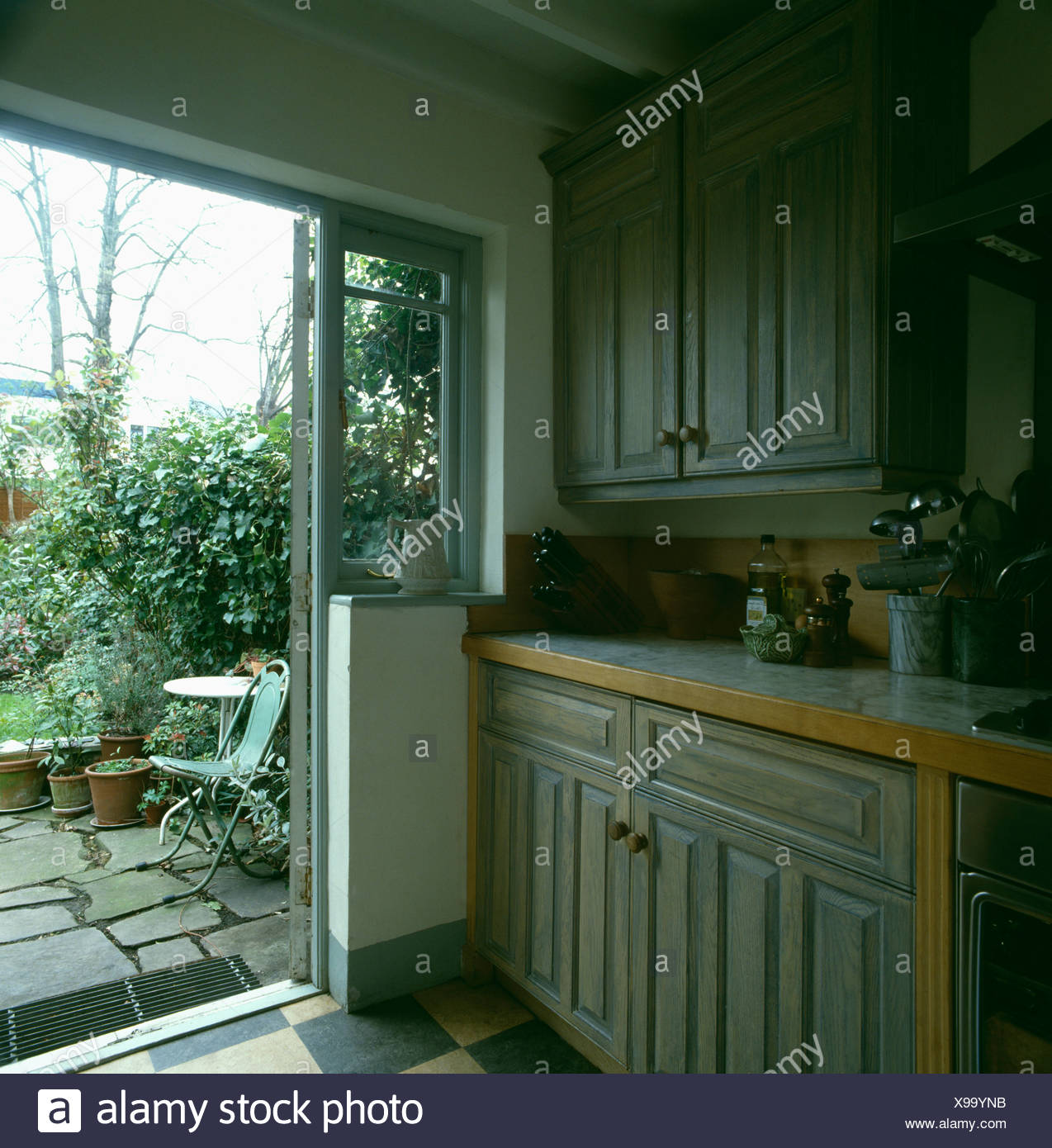Open Kitchen Gate: Pale Grey Wood-stain Units In Kitchen With Patio Door Open To The Garden Stock Photo: 281117127
