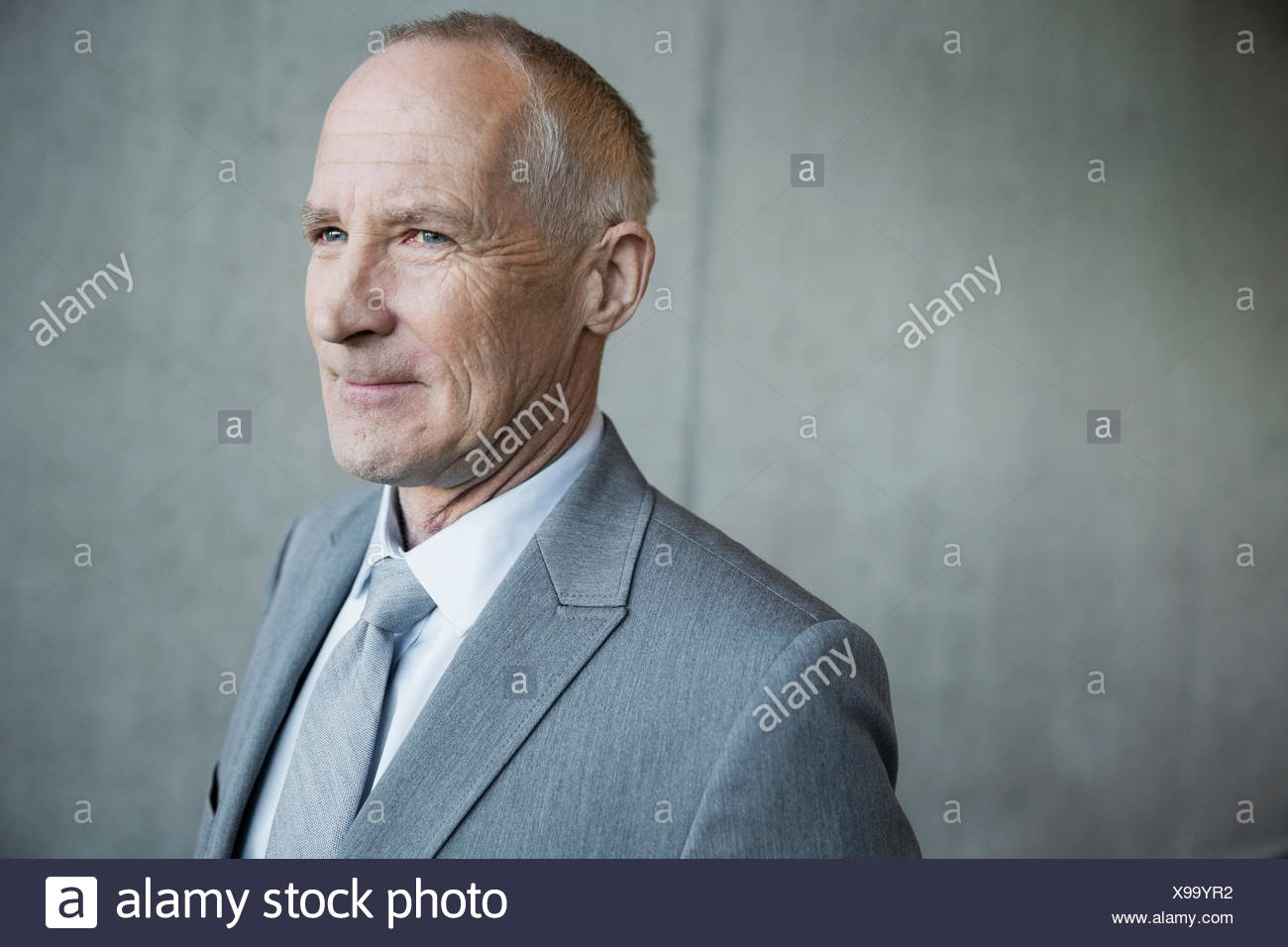 Confident businessman suit gray hair looking away - Stock Image