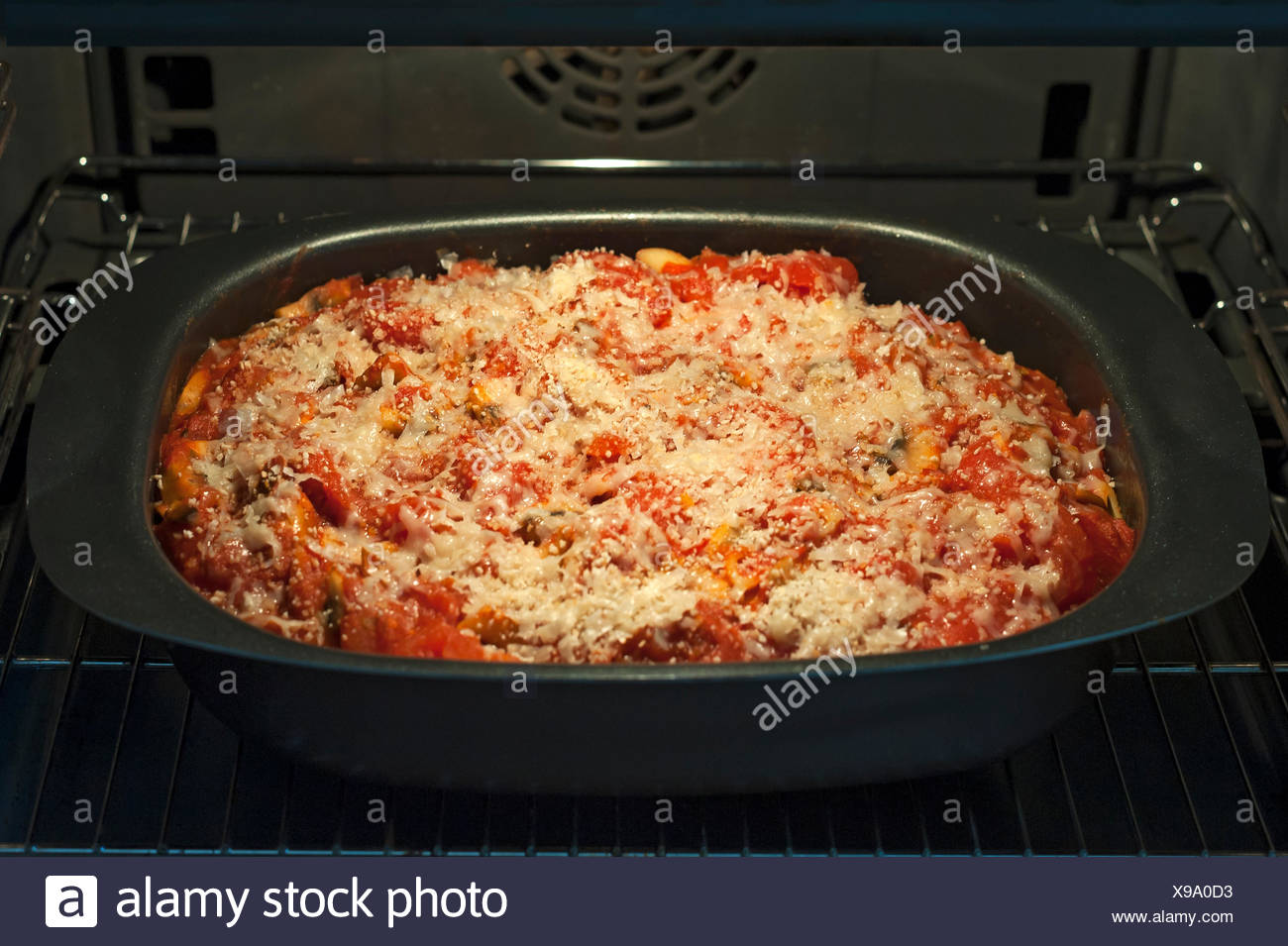 Baked pasta dish with tomato and cheese, in a pan in the oven Stock Photo