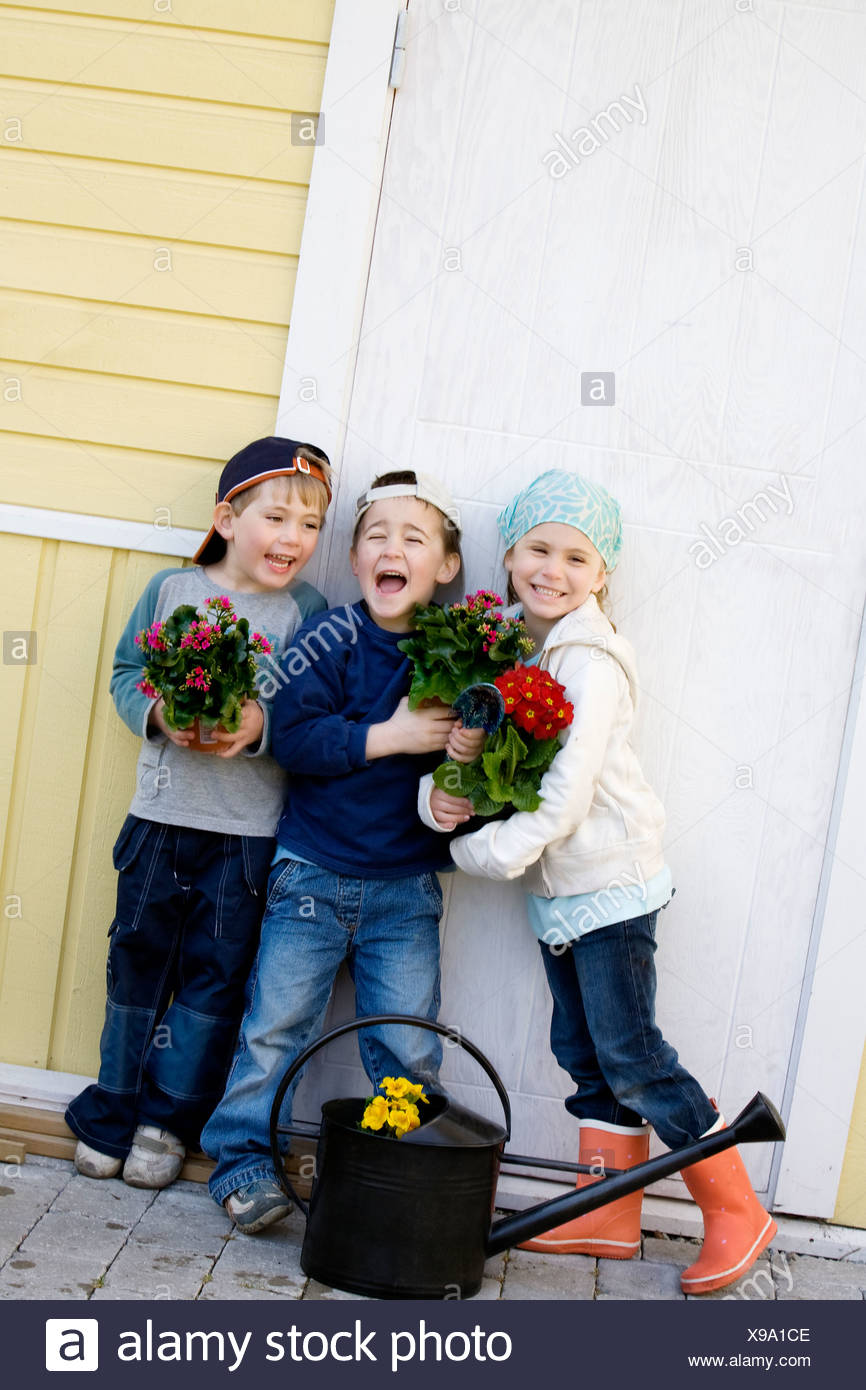 Three children with flowers. - Stock Image