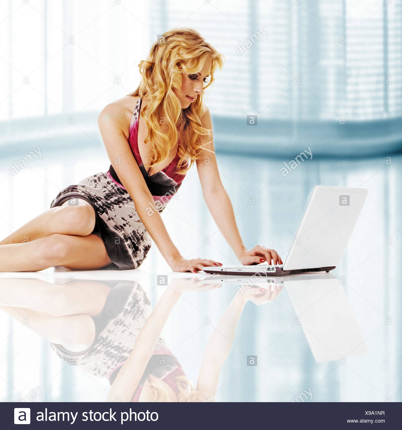 Beautiful girl on floor with laptop - Stock Image