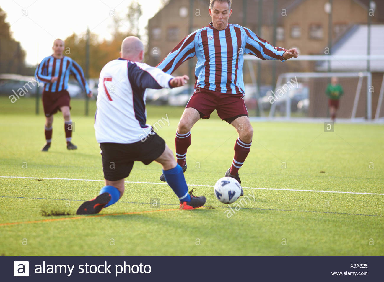 Football players fighting for ball - Stock Image