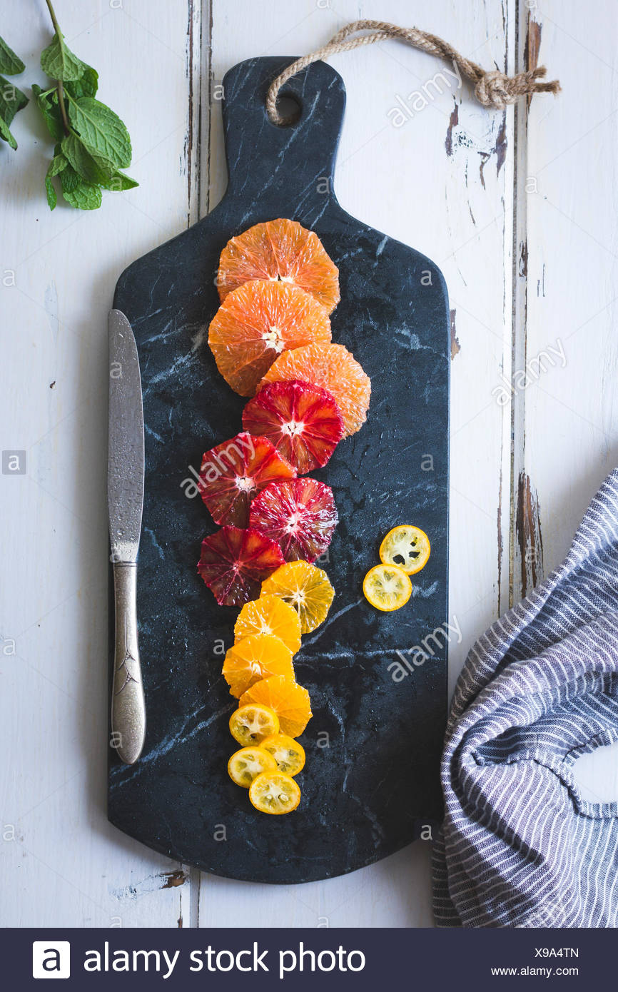 Citrus fruits on a marble chopping board. - Stock Image