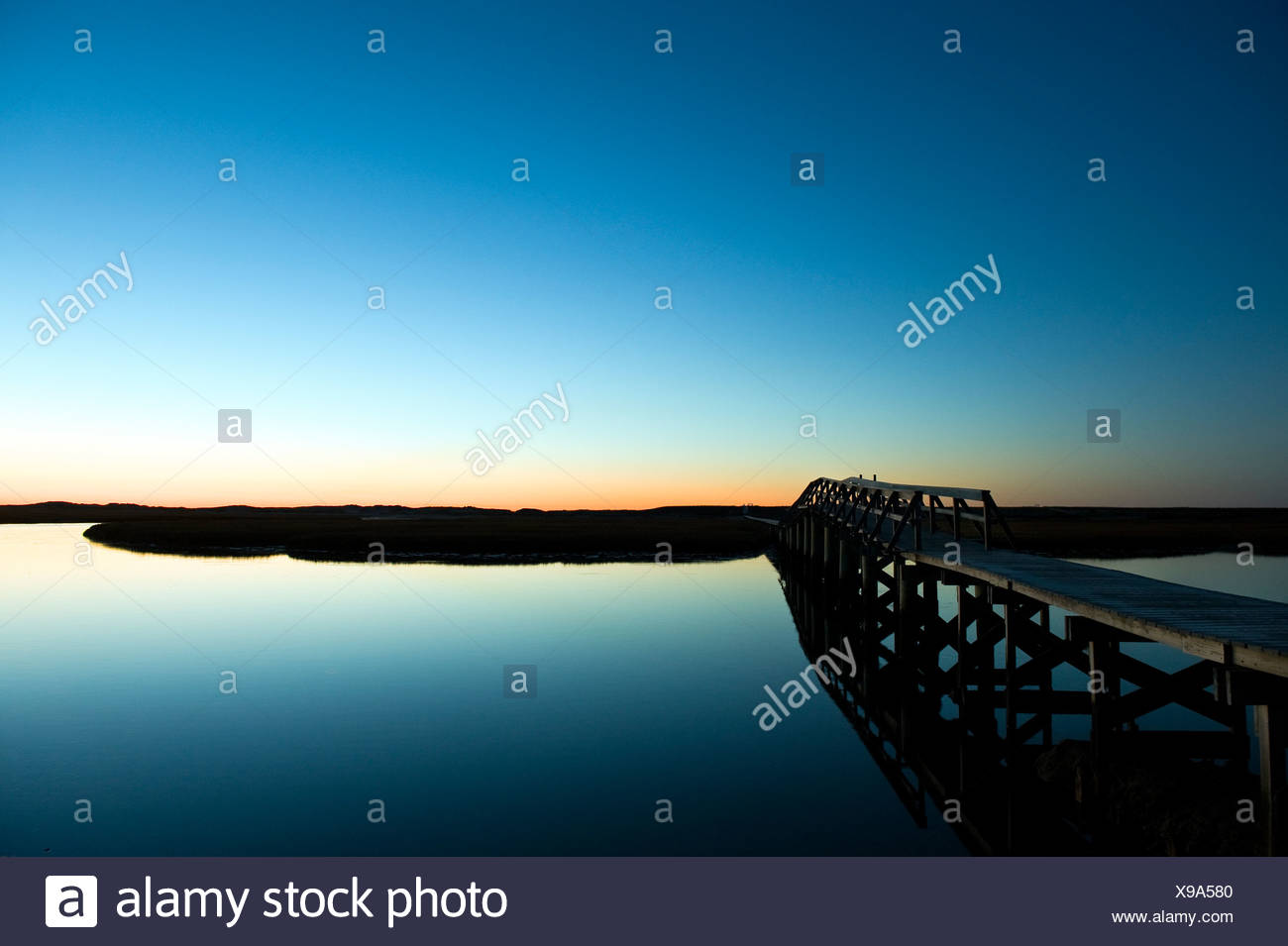 Boardwalk extending over the salt pond and marsh to the beach Sandwich Cape Cod - Stock Image