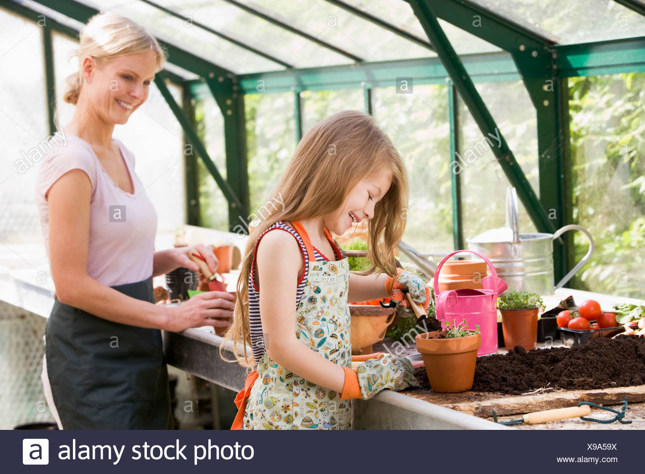 Young girl and woman in greenhouse putting soil in pots smiling Stock Photo