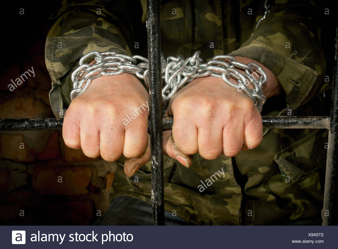 Man with hands tied up with chain - Stock Image
