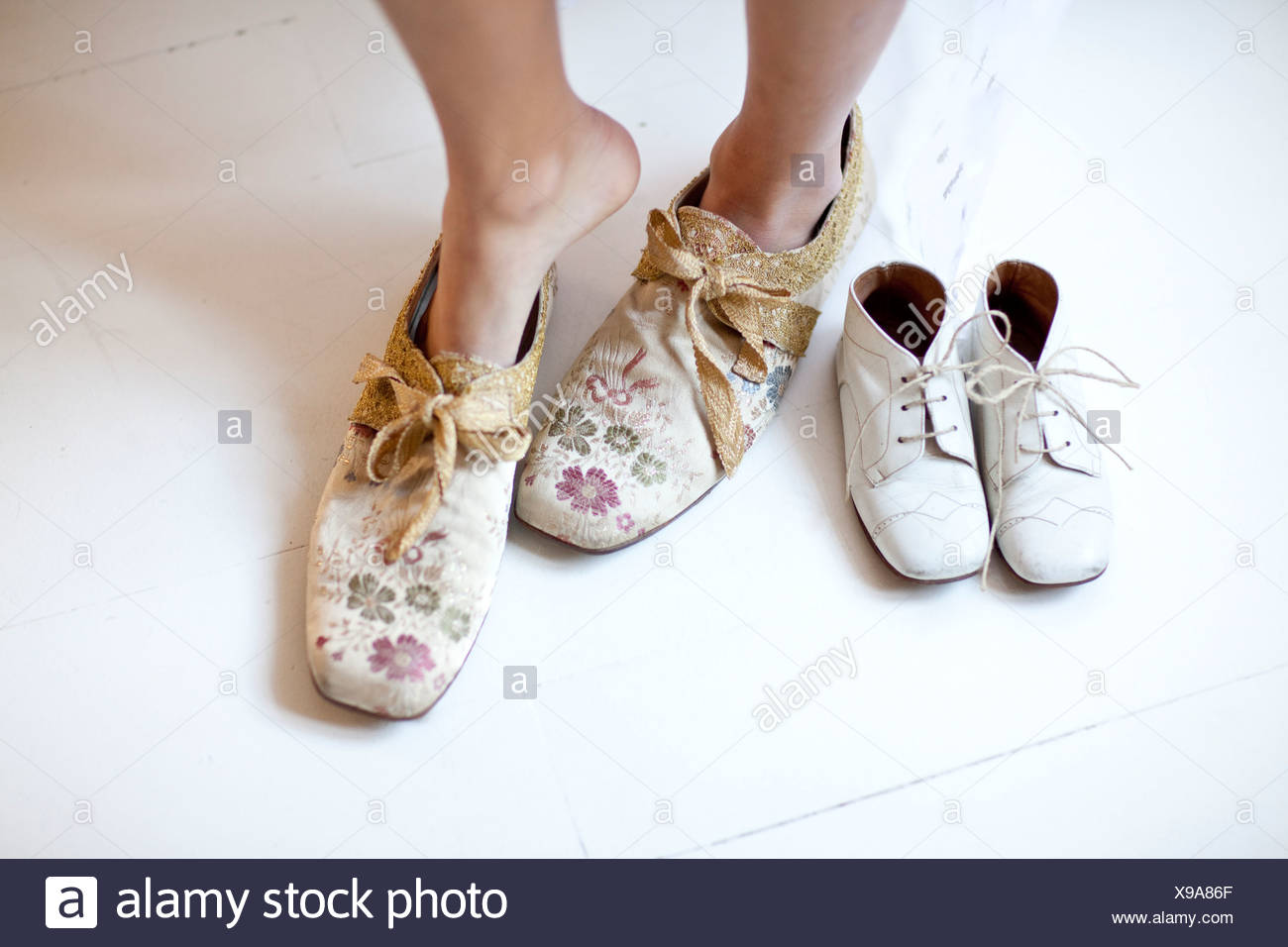 Woman putting on floral shoes Stock Photo