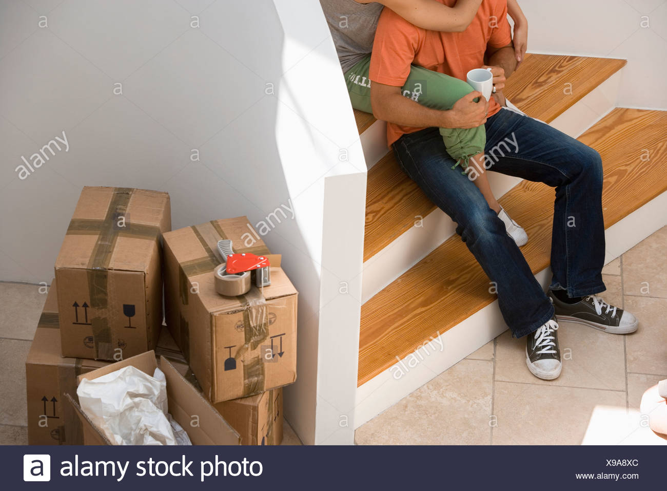 Couple sitting at bottom of staircase at home stack of packed boxes beside wall low section - Stock Image