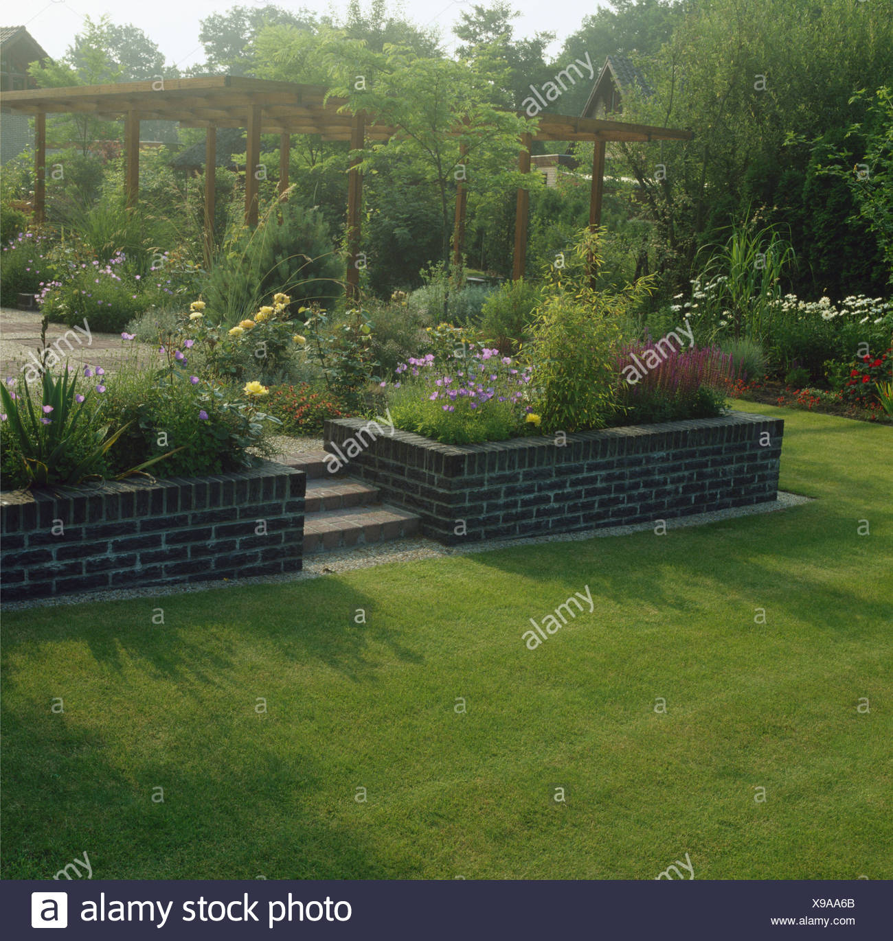 Lawn In Front Of Steps To Raised Patio Area With Pergola In Large Country  Garden