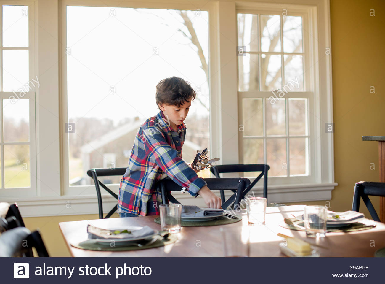 A young boy setting the table with cutlery and glasses. - Stock Image
