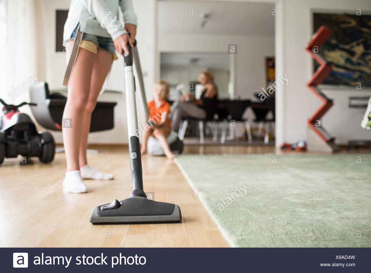 Low section of girl cleaning floor with vacuum cleaner at home - Stock Image