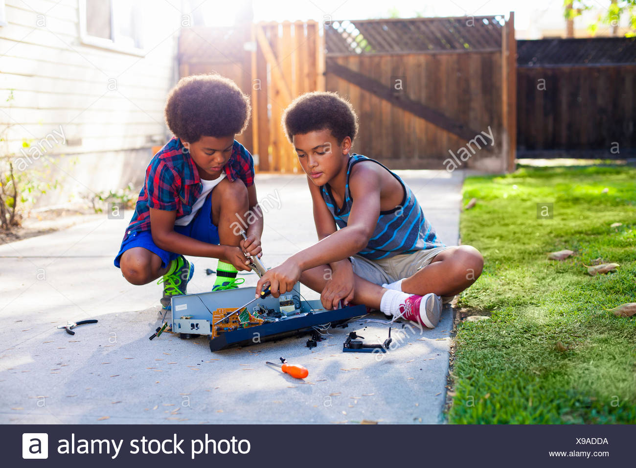 Two brothers dismantling electronic equipment in garden - Stock Image
