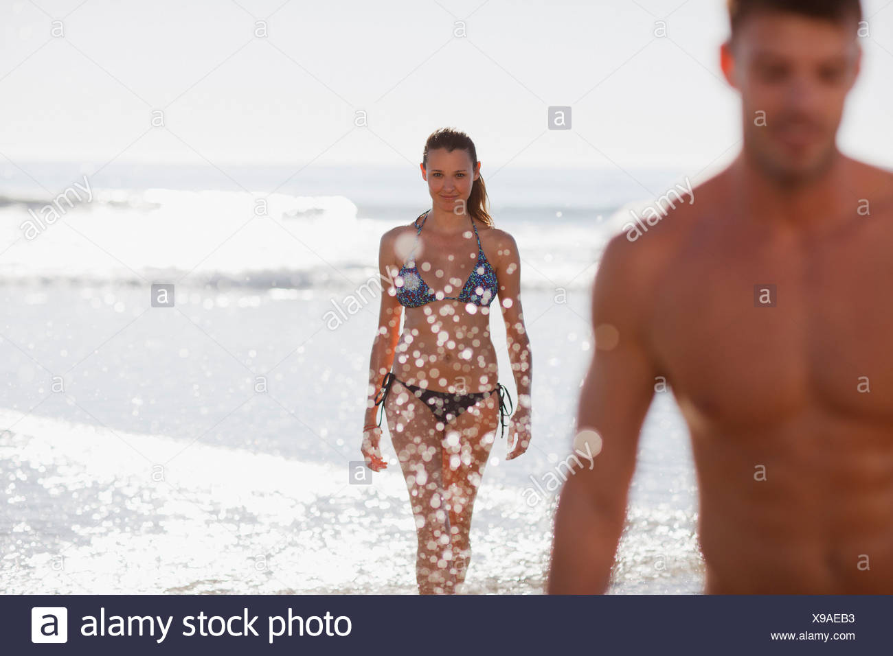 Woman in bikini walking in waves - Stock Image