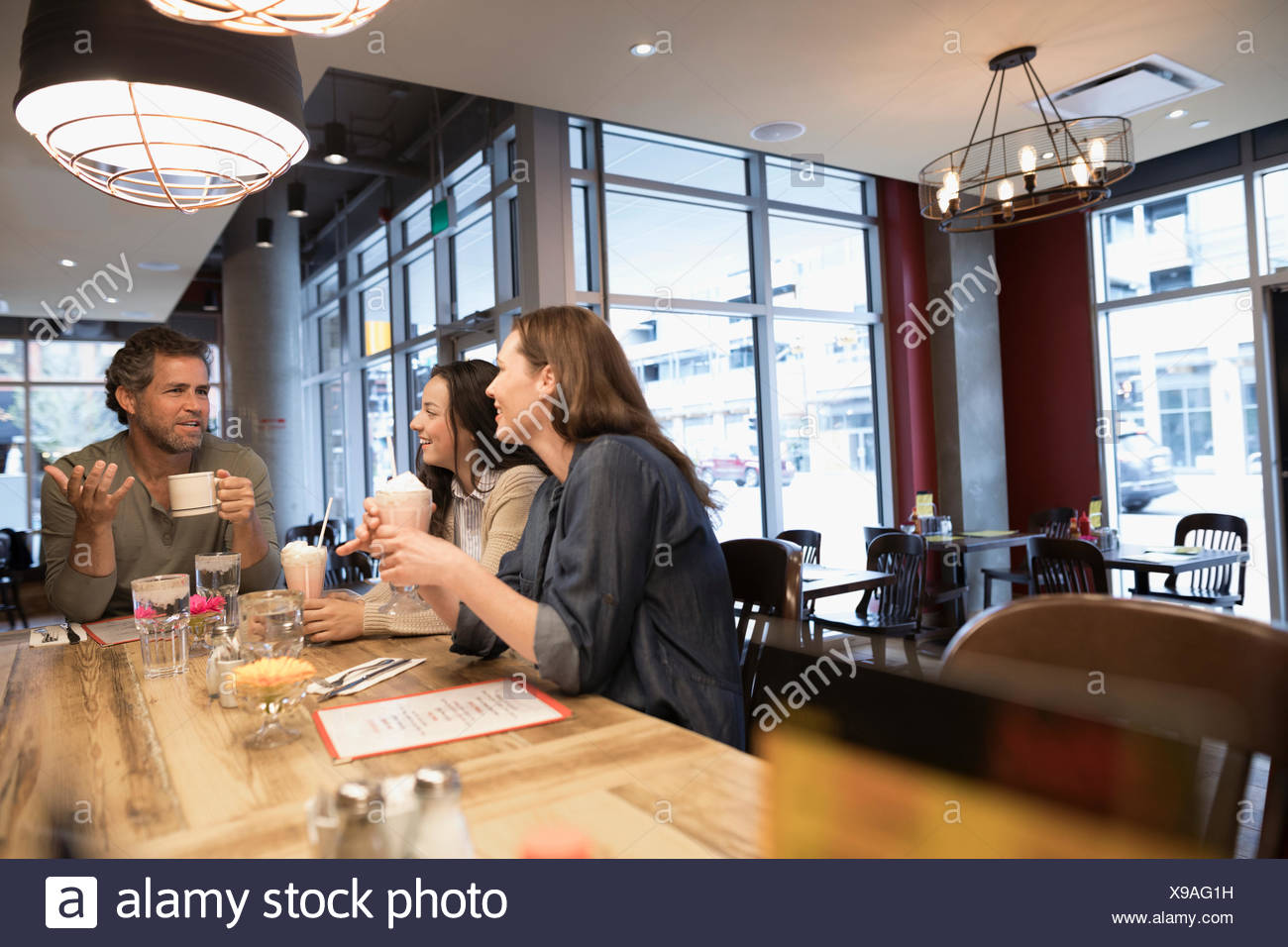Parents and teenage daughter drinking coffee and milkshakes at diner counter - Stock Image