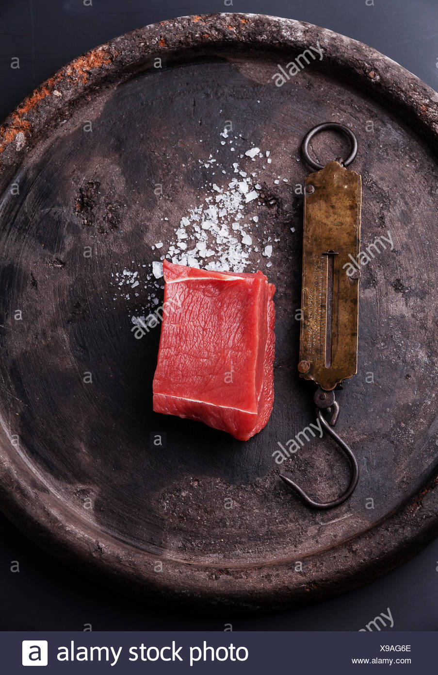 Raw fresh meat fillet and vintage steelyard on dark stone background - Stock Image