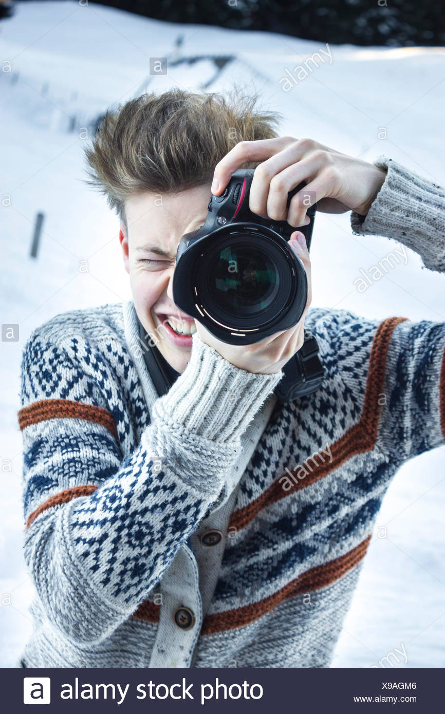 Young man in the snow taking a picture with a digital SLR camera, Hochbrixen, Brixen im Thale, Tyrol, Austria - Stock Image