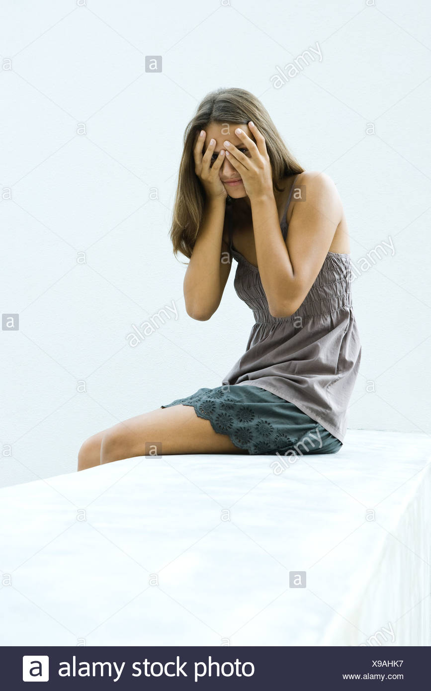 Teenage girl covering eyes with hands, peeking through fingers at camera - Stock Image