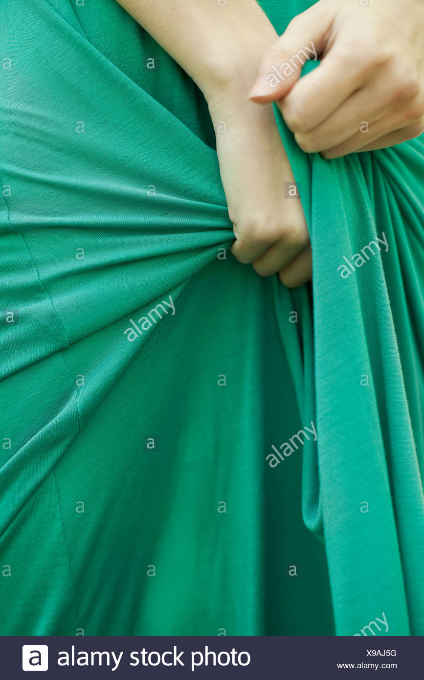 Woman clutching skirt of dress in hands, cropped - Stock Image